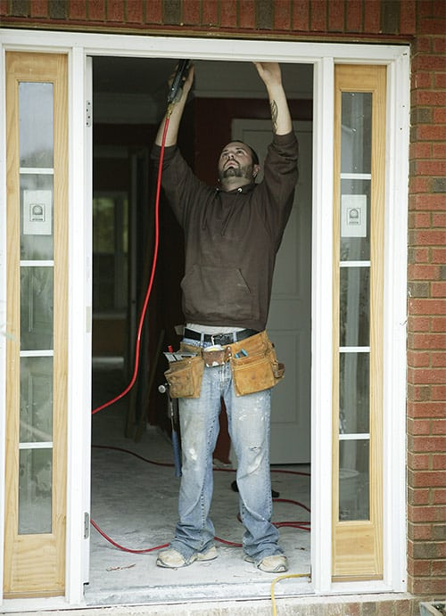 Licensed locksmith repairing a door that has been damaged by a break-in