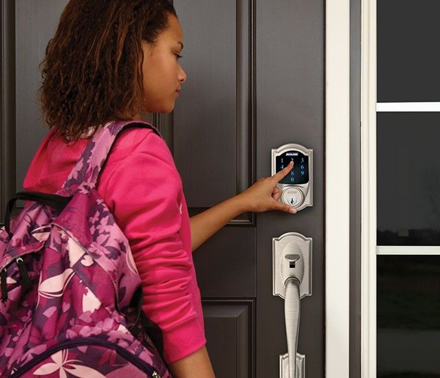 image of a young woman opening her home's front door using the smart lock keypad